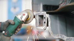 Работник мелет отрезок на автомобиле Ремонтные услуги автомобиля снимая искры видеоматериал
