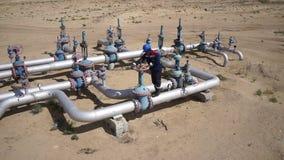 Работник месторождения нефти поворачивает клапан 60fps видеоматериал