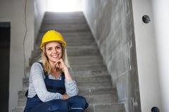Работник молодой женщины при желтый шлем сидя на лестницах на строительной площадке стоковое изображение