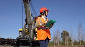 Работник молодой женщины стоит около экскаватора минирования, рассматривая проект видеоматериал