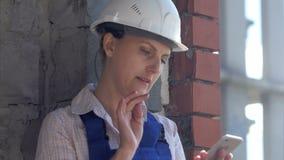 Работник молодой конструкции женский сидит на месте и работает на smartphone акции видеоматериалы