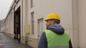Работник морского порта с бородой и шлемом идет задний взгляд