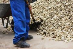 Работник нагружает гравий с лопаткоулавливателем в тачке пока ремонтирующ тротуар в городе стоковая фотография rf