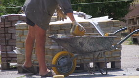 Работник нагружает покрашенный вымощая камень в тачке видеоматериал