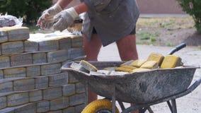 Работник нагружает покрашенный вымощая камень в тачке акции видеоматериалы