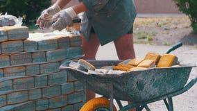 Работник нагружает покрашенный вымощая камень в тачке сток-видео