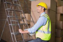 Работник на лестнице в складе Стоковое Фото