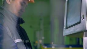 Работник на консоли управления, контрольная панель в складе Оператор работая с контрольной панелью 4K видеоматериал