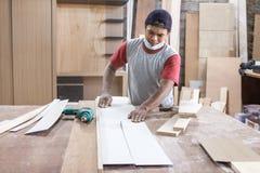 Работник на месте для работы плотника режа деревянное использование доски увидел t стоковое изображение