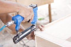 Работник на месте для работы плотника устанавливая ноготь используя пневматический na стоковые изображения rf
