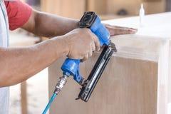 Работник на месте для работы плотника устанавливая ноготь используя пневматический na стоковая фотография rf