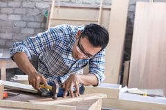 Работник на месте для работы плотника устанавливая ноготь используя молоток стоковая фотография