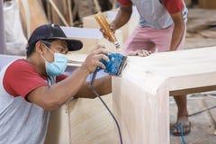 Работник на месте для работы плотника уточняя поверхность деревянной доски стоковая фотография