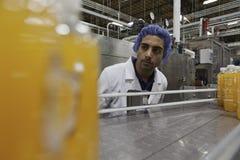 Работник на производственной линии смотря вниз с конвейерной ленты стоковое фото