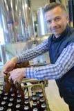 Работник на фабрике пива разливая по бутылкам Стоковая Фотография