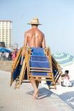Работник носит deckchairs для того чтобы положить их прочь в конце дня Стоковое Фото