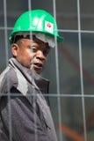 Работник нося зеленый шлем и смотря камеру Стоковое Фото