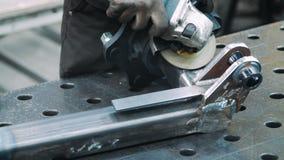 Работник обрабатывая поверхность части металла с угловой машиной в мастерской сток-видео