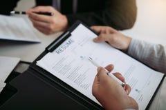 Работник описывает опыт работы в бумаге резюма для менеджера на офисе стоковая фотография