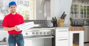 Работник доставляющий покупки на дом держа коробки пиццы в кухне Стоковая Фотография