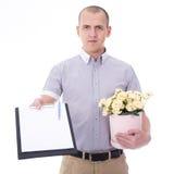 Работник доставляющий покупки на дом держа доску сзажимом для бумаги и пук цветков изолированных дальше Стоковые Изображения
