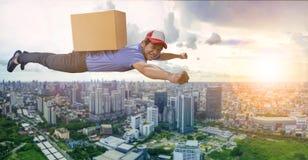 Работник доставляющий покупки на дом летая над scape города с коробкой контейнера дальше назад, Стоковые Фотографии RF