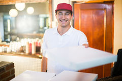 Работник доставляющий покупки на дом пиццы давая коробки пиццы Стоковое фото RF