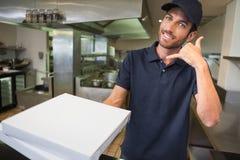 Работник доставляющий покупки на дом пиццы держа коробки пиццы делая телефон для того чтобы показывать Стоковые Изображения RF