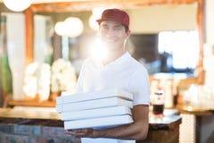 Работник доставляющий покупки на дом пиццы держа коробки пиццы Стоковое Фото