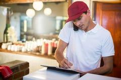 Работник доставляющий покупки на дом пиццы принимая заказ над телефоном Стоковое Изображение RF