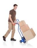 Работник доставляющий покупки на дом с ручной тележкой и коробками Стоковая Фотография