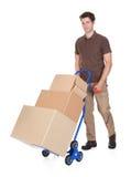 Работник доставляющий покупки на дом с ручной тележкой и коробками Стоковое фото RF