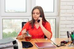 Работник офиса выпивает чай на рабочем месте и беседы по телефону стоковое изображение rf