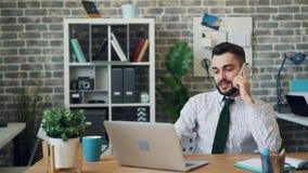 Работник офиса говоря на мобильном телефоне и используя деятельность ноутбука самостоятельно сток-видео