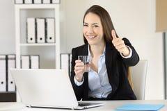 Работник офиса держа стекло воды смотря вас Стоковые Фотографии RF