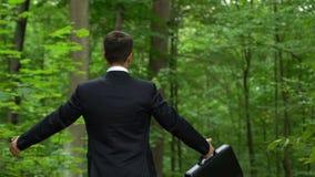 Работник офиса идя в лес с портфелем, поворачивая кругом и дыша глубоко сток-видео