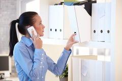 Работник офиса на мобильном телефоне выбирая скоросшиватель архива Стоковые Изображения RF