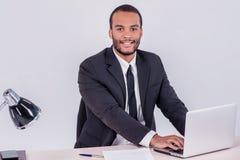 работник офиса предпосылки зеленый Усмехаясь африканский бизнесмен сидя на таблице Стоковое Изображение RF