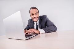работник офиса предпосылки зеленый Усмехаясь африканский бизнесмен сидя на столе дальше Стоковые Изображения