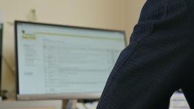 Работник офиса работает на компьютере видеоматериал