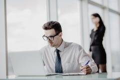 Работник офиса сидя на столе в офисе используя компьтер-книжку, пока женщины говоря телефон на заднем плане Стоковая Фотография