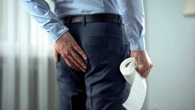 Работник офиса с туалетной бумагой в руке страдая от боли геморроя, поноса стоковая фотография rf
