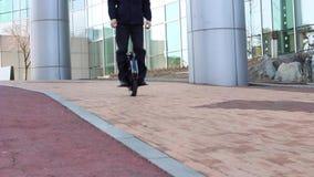 Работник офиса управляет на электрическом mono колесе около делового центра видеоматериал