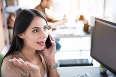 Работник офиса Astonished усмехаясь женский держа smartphone Стоковые Фотографии RF