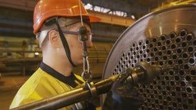 Работник очищает трубки с сверля инструментом на машине акции видеоматериалы