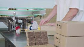 Работник пакует стеклянные опарникы с соусом песто в картонную коробку на фабрике еды сток-видео