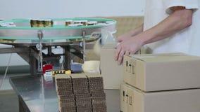 Работник пакует стеклянные опарникы с соусом песто в картонную коробку на фабрике еды видеоматериал
