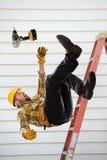 Работник падая от лестницы стоковое изображение