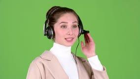 Работник поддержки говорит к клиентам на шлемофоне зеленый экран движение медленное видеоматериал