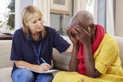 Работник поддержки навещает старшая женщина страдая с депрессией стоковое изображение rf
